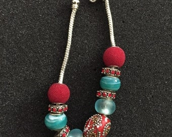 Assorted turquoise red and silver colors on a rope metal bracelet