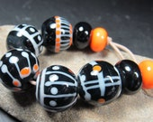 Black cream and tangerine round lampwork beads with fine stringer detail