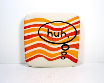 "tile with ""huh."" thought bubble on orange and red-orange waves. Ready to ship."