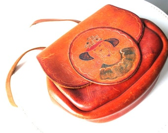 boho vintage 70s caramel-brown hand tooled  saddle,cross body, rounded  bag with a large flap ad portrait of the lady with a flolwer hat.