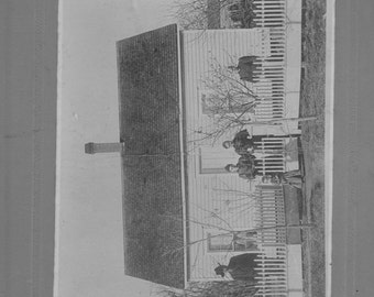 Early 1900s cardboard photo.of a family standing  in front of the old homeplace