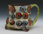 Purple and red dots with tan and green checkered background footed fluted wavy style mug