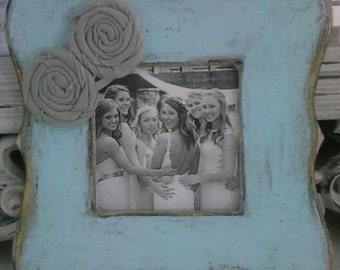Turquoise distressed wood picture frame with grey rosettes