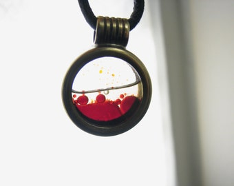 Blood sample pendant. Fluid in motion. Handcrafted from brass and glass.