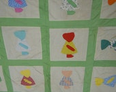 Quilt top: Sunbonnet Sue with hand appliqued color coordinated Sues and green sashing and borders