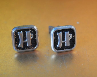 """Mod vintage 60s """"washed"""" gold tone metal cuff links with a black enamel and letter H."""