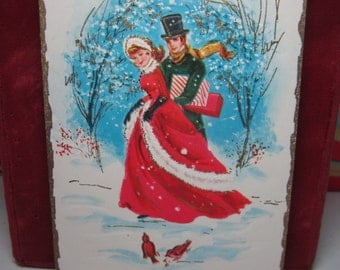 1950's-60's embossed gold gilded christmas card with attractive victorian couple walking through a snowy woods holding gifts admiring birds
