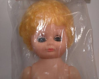 In package plastic doll, movable eyes, yellow hair