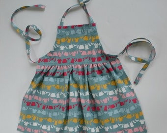 Toddler's/girl's apron, gift idea, clothes on washline, whimsical print, adjustable apron, apron with pockets, gathered apron, sizes 1 to 6.