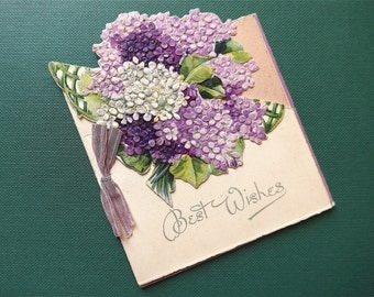 Christmas card, vintage, it has a cut-out flip front featuring a spray of Lilacs, lilac ribbon bow trim. used.  c 1915.