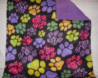 Doggy Blanket - colorful large patterned paws print fleece with solid lavendar on the reverse side.