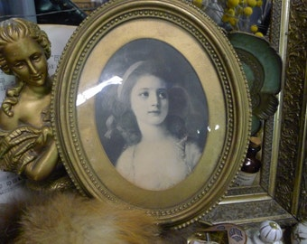 Portrait of a woman in gold oval frame