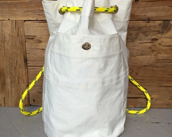 Recycled sail backpack, with dingy line, grommets and interior zip pocket.