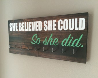 "Race Medal Holder - ""She believed she could SO SHE DID"" white and teal with wood grain background"
