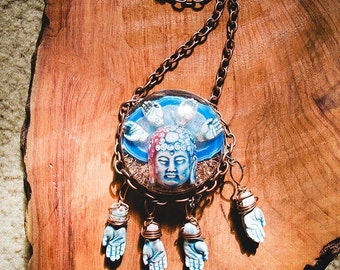 Blue Buddha head with hands against agate backing and copper shavings.