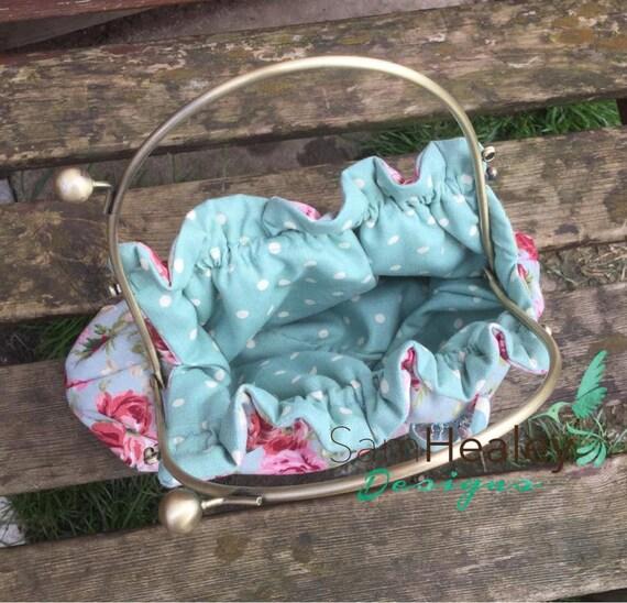 Vintage linen look floral fabric handbag, with brass effect clip top frame