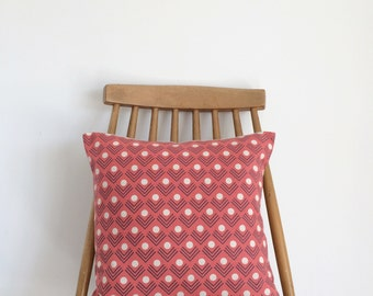 Coral/ red patterned, handmade cushion. Feather insert included.