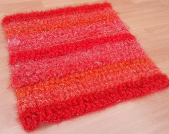 Acrylic wool in shades of red hand-woven rug