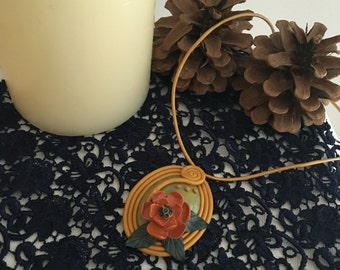 Gold pendant with green stone and orange flower
