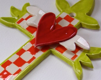 Bright whimsical ceramic Cross - Tangerine orange & chartreuse, checkered and a bright red sacred heart, wings