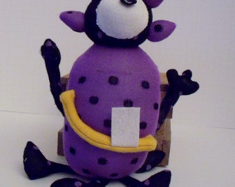 Sock Monster With One Bead Eye and Four Legs with Four Spikes on the Head and a Big One Tooth Smile Made From a Black and Purple Sock