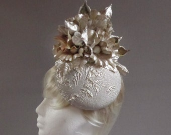 siver (ish) gold (ish) hat with endorment of leaves , flowers and.....brachiton seed shells on comb