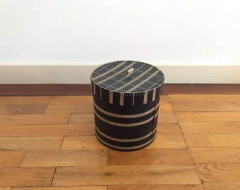 Small vintage cardboard hat box or storage box in dark blue with off-white decorative horizontal bands