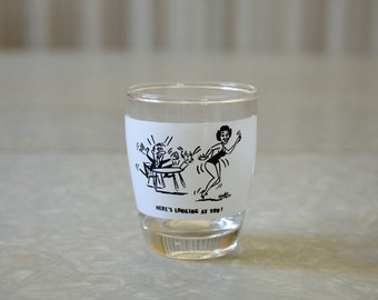Vintage funny shot glass with man watching a lady dancer, Here's looking at you! signed Handis