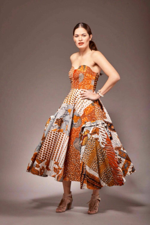 "The dress features a traditional African design with short skirt and off-the-shoulder, elastic sleeves. It is available in black, green, orange, pink, purple, red or yellow. The dress is 31"" in length and the elastic bust fits up to a 46"" bust."