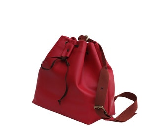 Red leather bucket bag is a multi way bag: backpack, shoulder bag or cross body bag