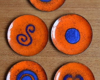Set of five metal coasters with enamel coating in blue and orange