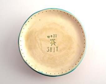 small plate/saucer with cussing and bug stamps