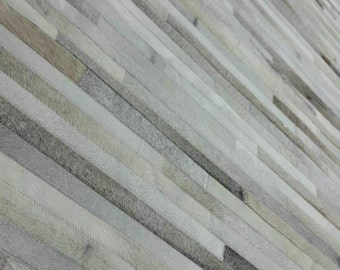 Patchwork Cowhide Rug, Mix of Greys, Creams and whites. Model Strip 5' x 7'