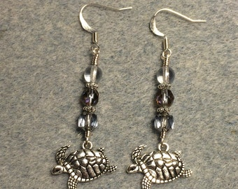 Silver swimming sea turtle charm earrings adorned with light blue Czech glass beads.