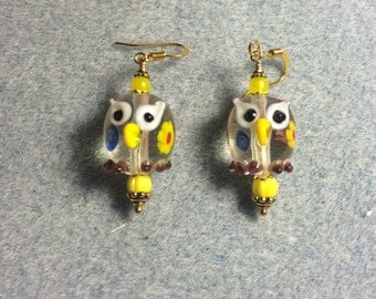 Clear spotted lampwork owl bead earrings adorned with yellow Czech glass beads.