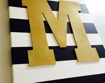Black and white canvas with gold letter of choice