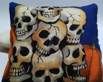 Lavender sachet pillow with pile of skulls.