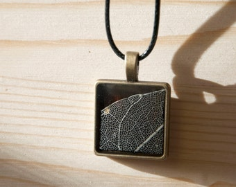 Handmade necklace with pendant made of metal, resin and real skeleton of leaf