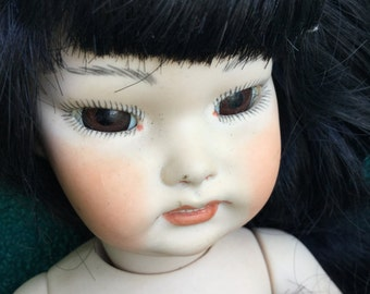 Lovely Asian Bisque doll with 3 clothing articles