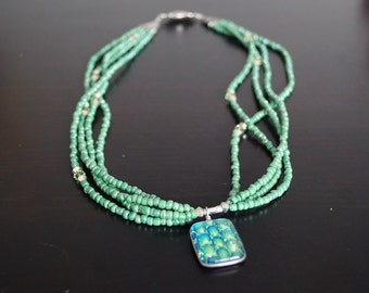 Green multistrand necklace with sparkly pendant
