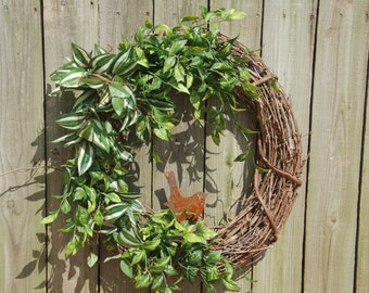 Rusty bird with natural look foliage on grapevine wreath