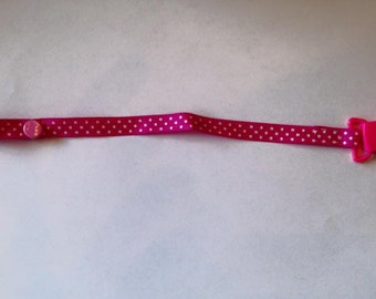 Pink pacifier clip with white dots.