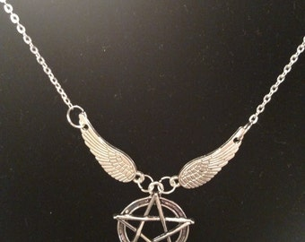 This necklace features silver wings flying away with a pentagram.