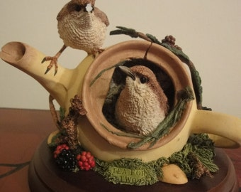 two sparrows nesting in old tea cup  standing on wooden plinth 6 inches high