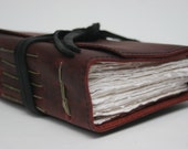 Deep purple leather journal with classic leather strap and handmade paper
