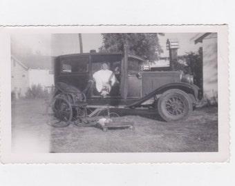 original 1920-30s photo. cripple man getting out of a antique car into a antique wheelchair