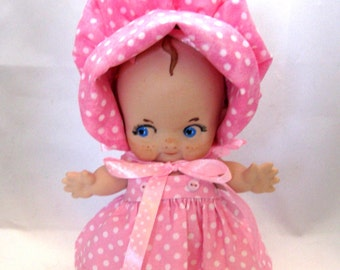 "Cupie/kewpie 8"" doll cast in porcelain from a vintage mold wearing a pink polka dot dress and bonnet"