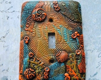 Hidden Glyphs, switch plate cover, polymer clay, blue, orange, greens, gold and black accents