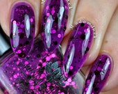 "Nail polish - ""Shades of black""  Black and pink dots in a dark purple jelly base"
