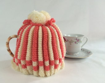 Coral and cream pom-pom tea cozy